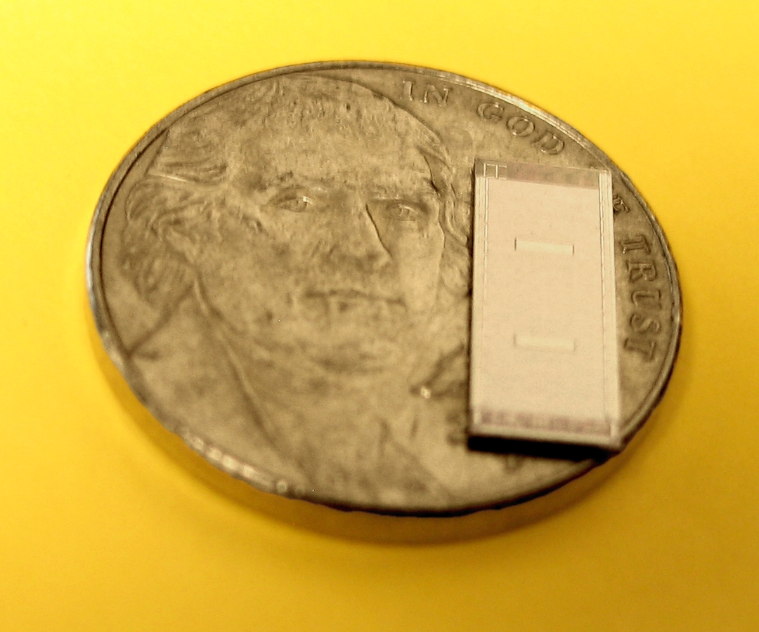 A two-layer die (with nickel for scale)